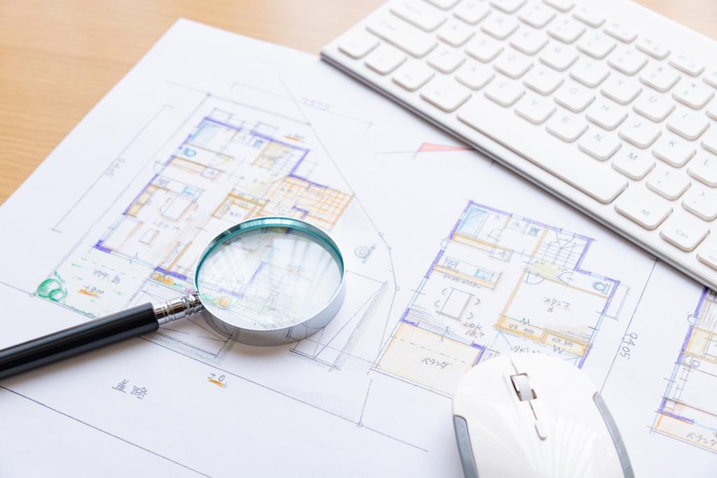 放大鏡、電腦鍵盤及住家室內平面圖