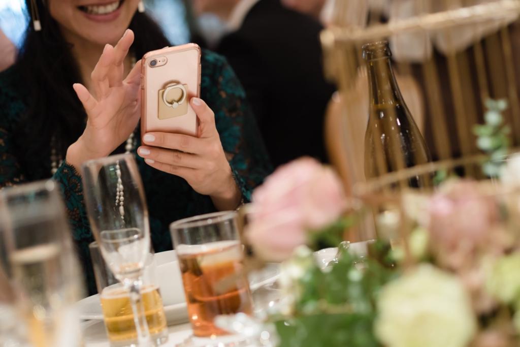 婚禮上一邊吃飯一邊開心滑手機的女子