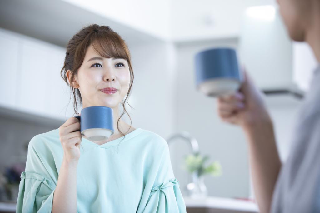手拿藍色茶杯的女性