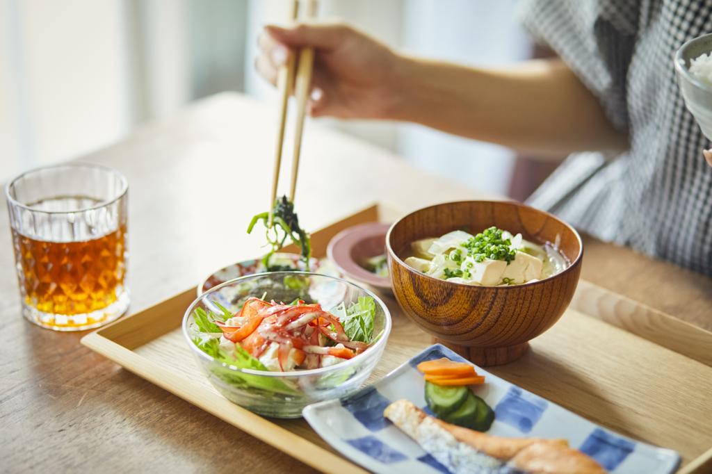 右手拿筷子夾定食中配菜的人