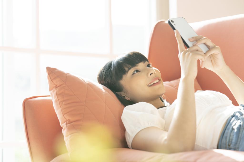 女性躺在橘紅色沙發上滑手機