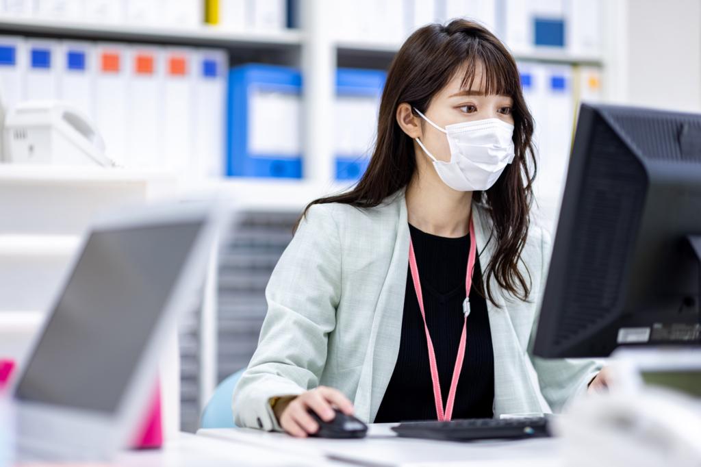 戴著口罩的職員正在面對電腦工作