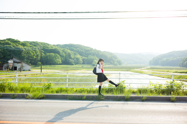 young high school japanese girl walking across a bridge in the japanese countryside