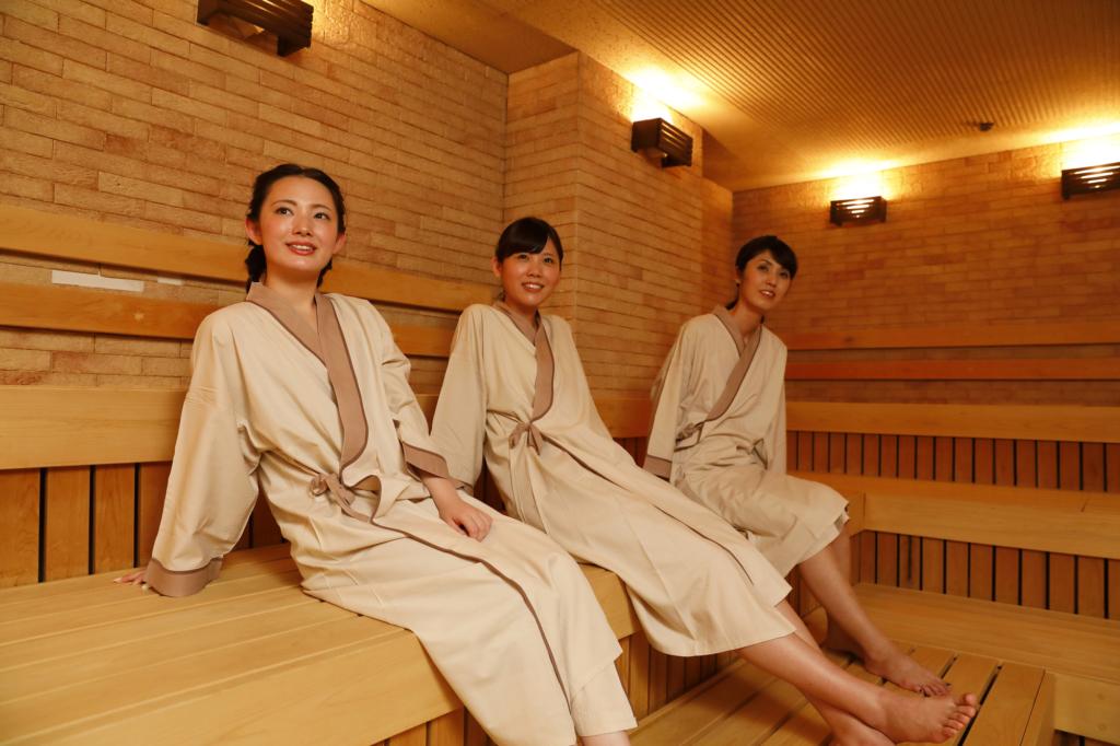 三個穿浴袍的女生坐在桑拿房裡
