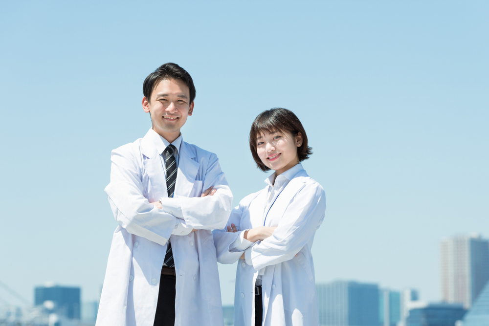 Smiling male and female doctors in white coats