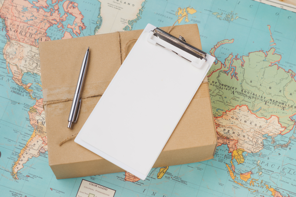 Pen and clipboard on package with world map underneath