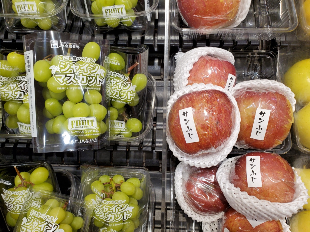 Grapes and apples wrapped in plastic in grocery store