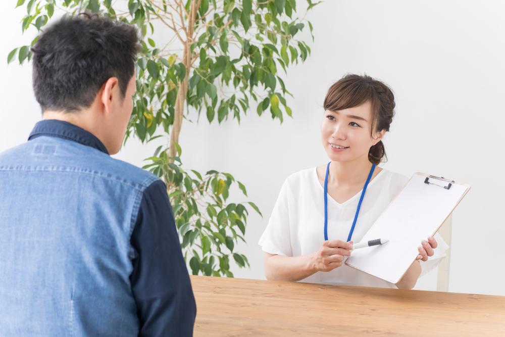 女子拿著文件正向男子推薦新工作