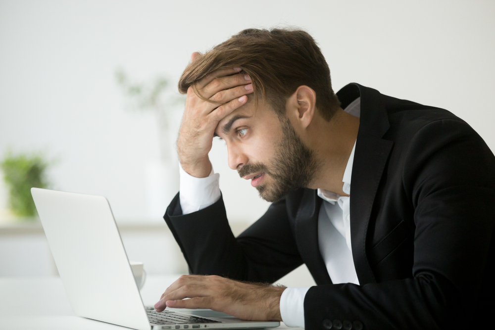 man stressed at his laptop