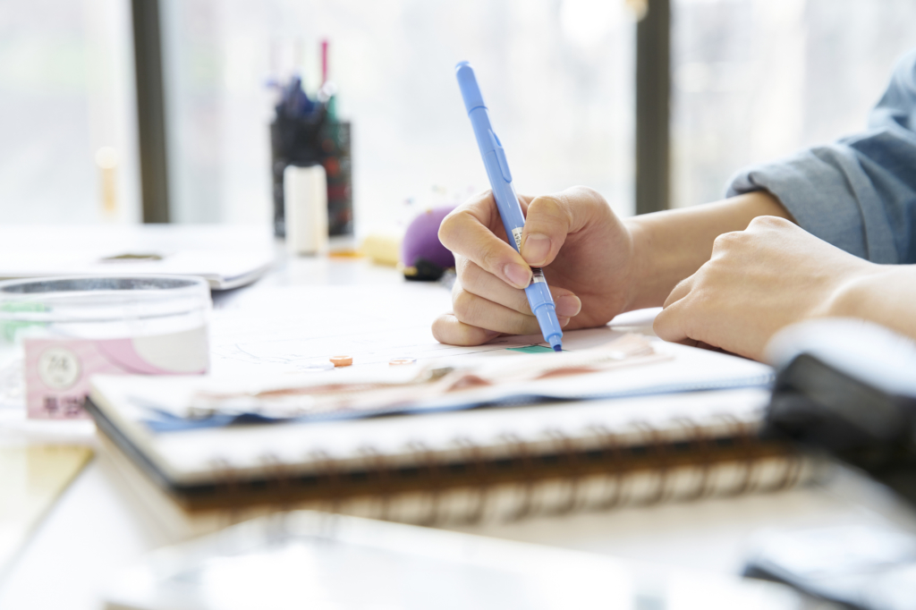 一個人拿筆在筆記本上畫畫書寫