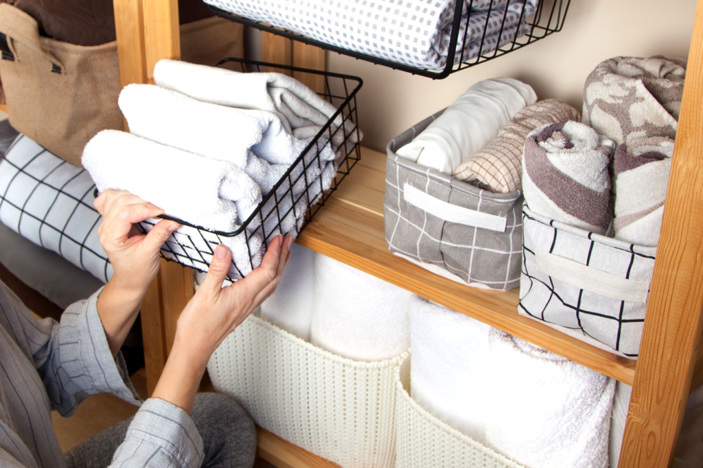 Woman organizing folded towels in containers