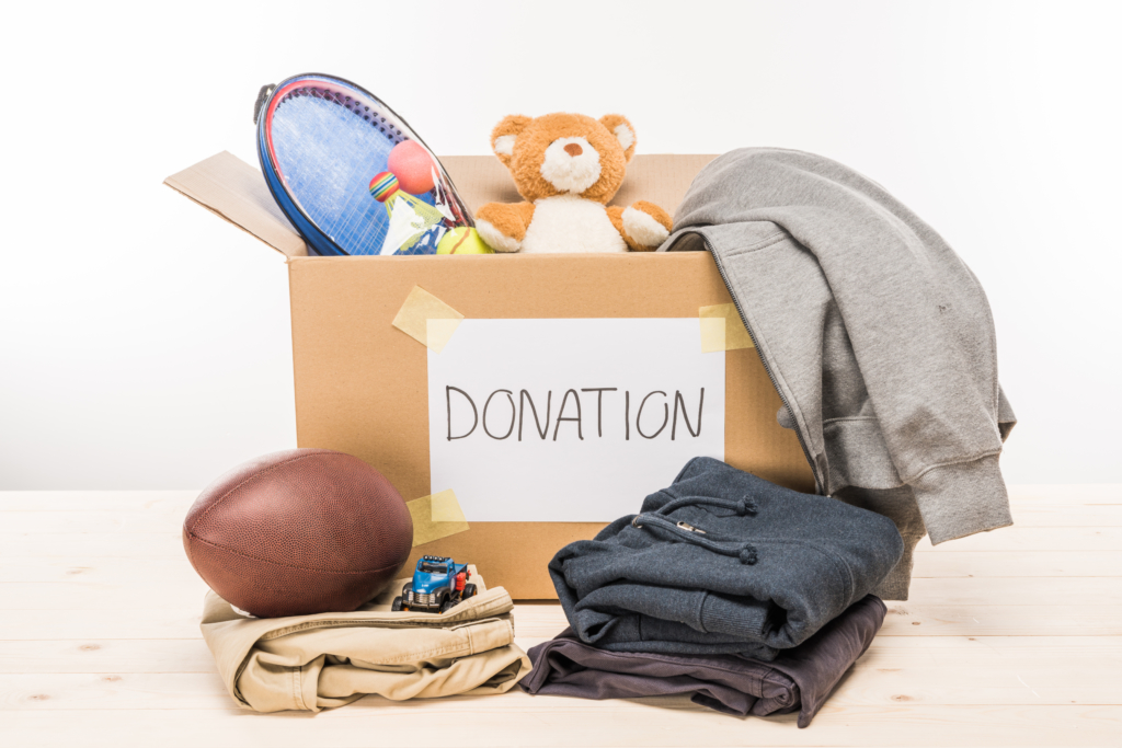 Clothes and toys in and in front of cardboard box for donation