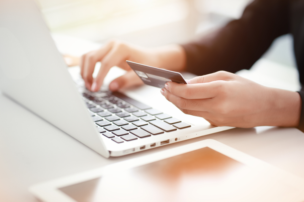 Person using laptop and holding credit card