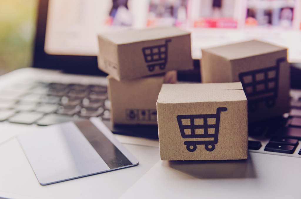 Plastic card and small cardboard boxes with shopping cart motif on laptop