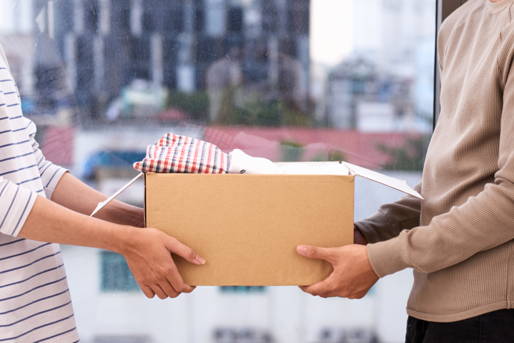 Two people holding cardboard box full of clothes