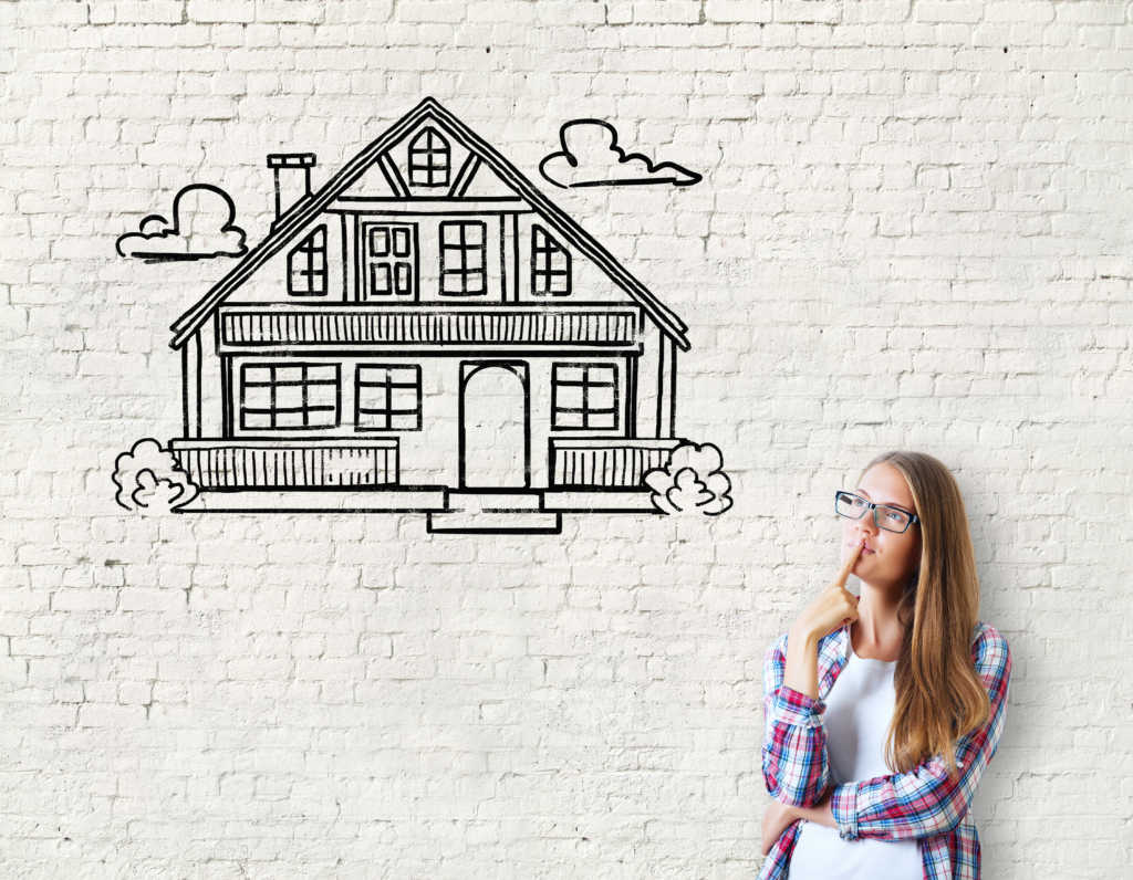 lady thinking about a home while leaning against a brick wall