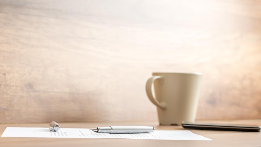 桌上擺著手機咖啡筆及文件