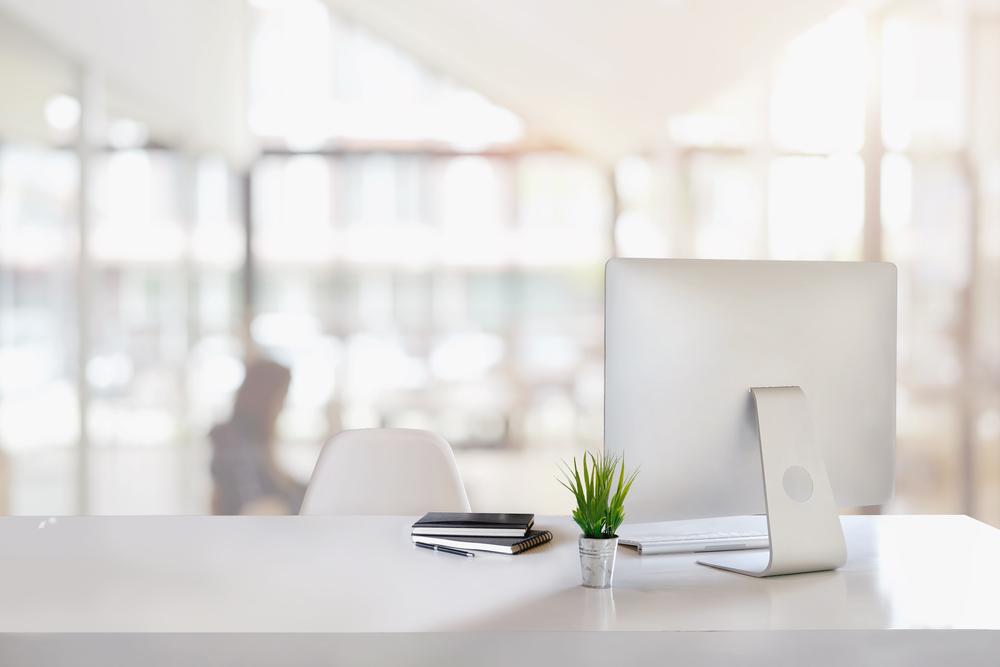 潔白明亮的開放式辦公桌,桌上有電腦筆記本跟植物