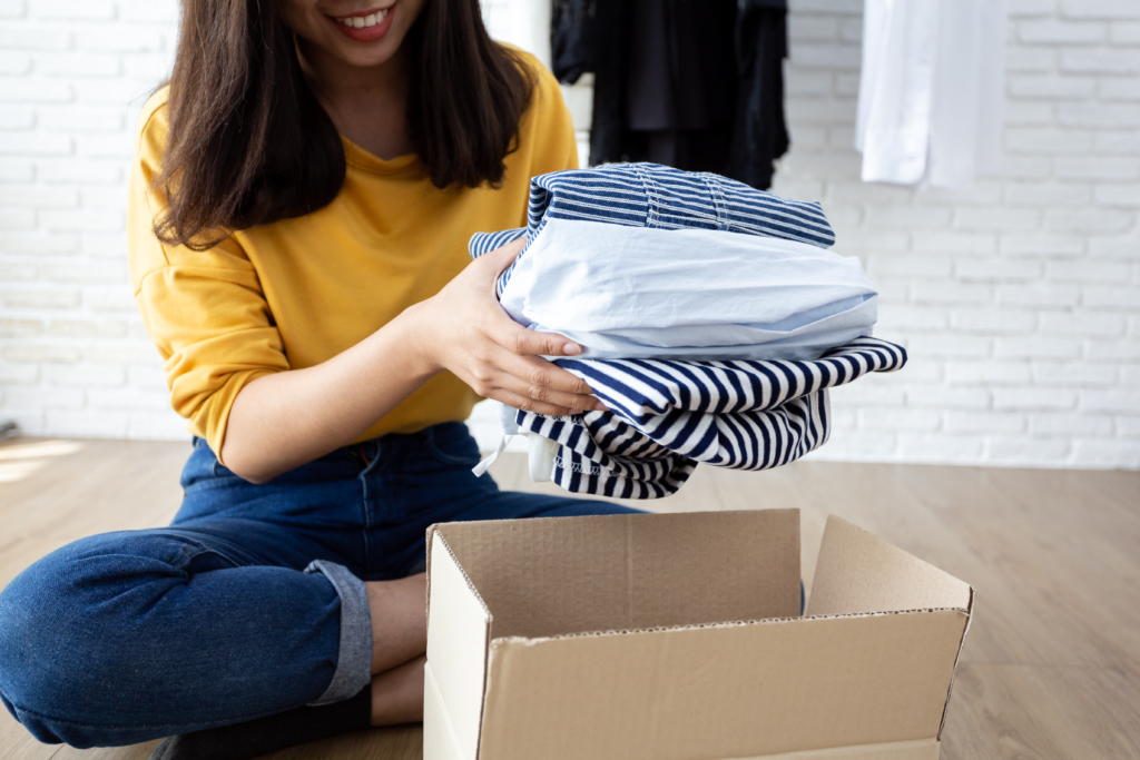 Woman putting clothes into cardboard box