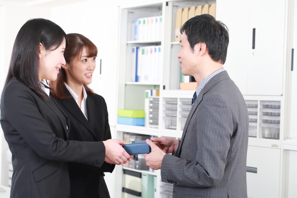 Office women handing chocolate to salaryman