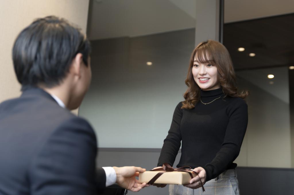 Woman handing boss chocolate