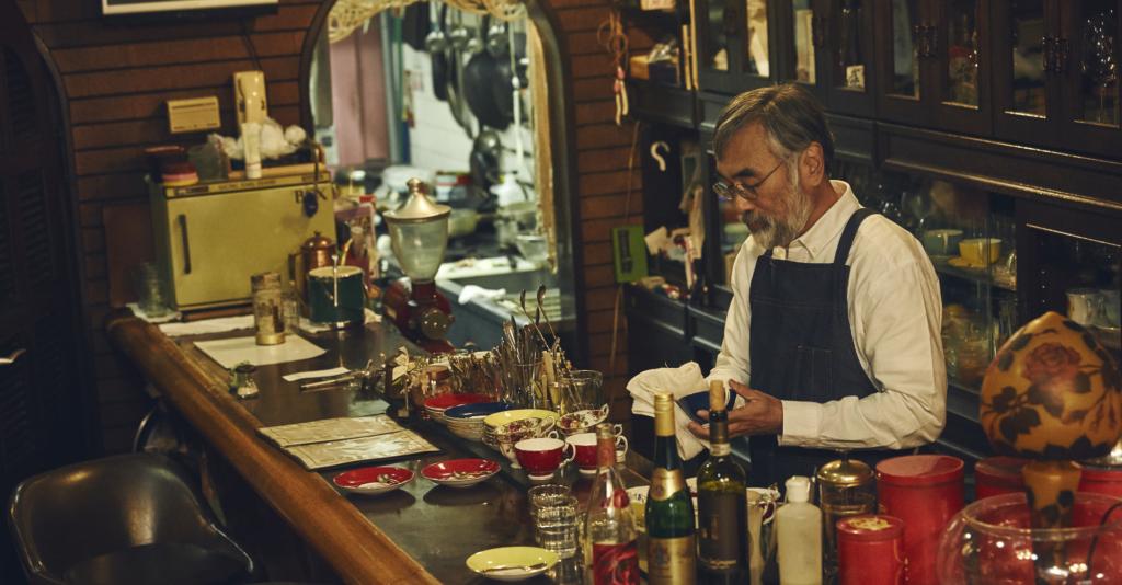 吃茶店裡戴著眼鏡頭髮白灰的店主穿著圍裙正在吧台後擦杯子
