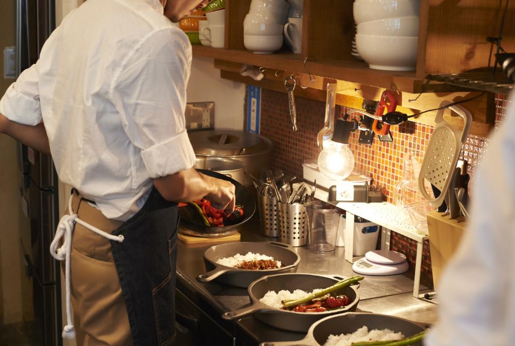 咖啡廳的廚房後台男子正在忙著下廚炒菜