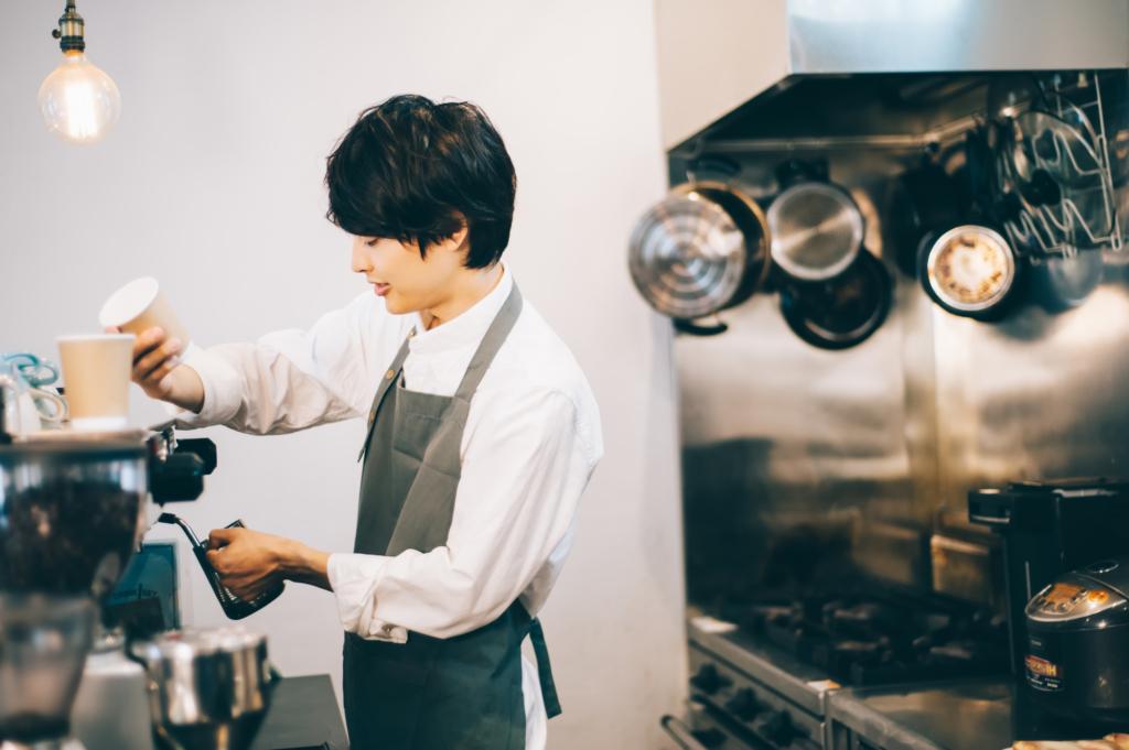 穿著圍裙的男子正在煮咖啡