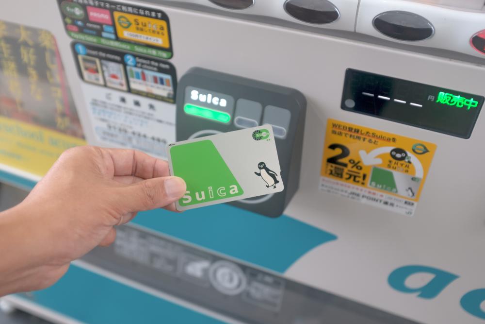 一隻手拿suica卡在自動販賣機的結帳區感應卡片