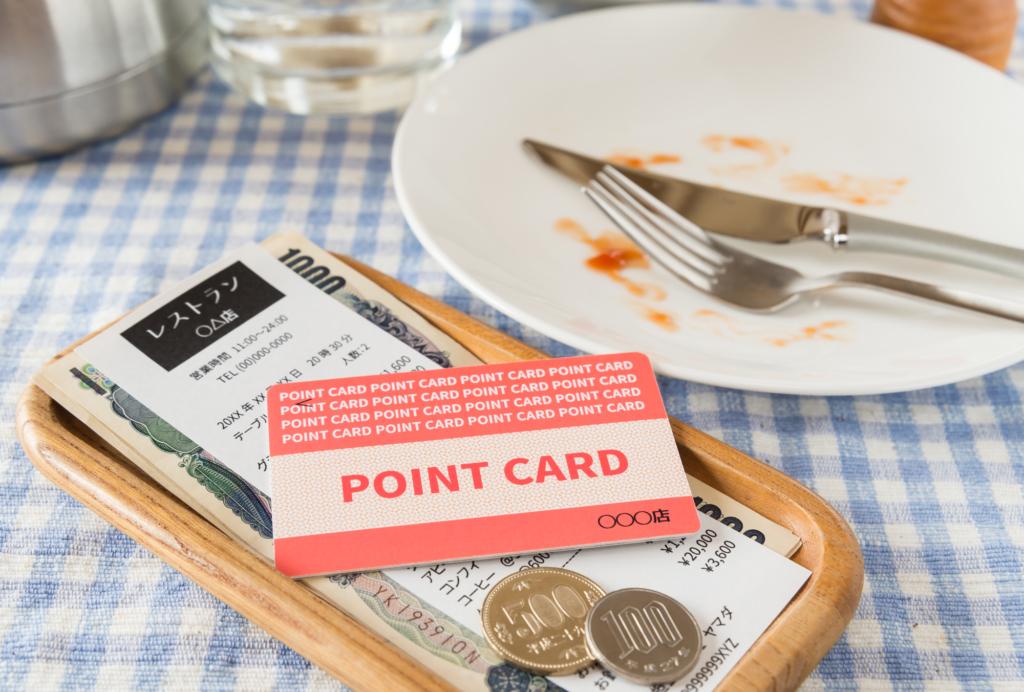 餐桌上擺放著剛吃完的空盤和日幣紙鈔零錢和點數卡
