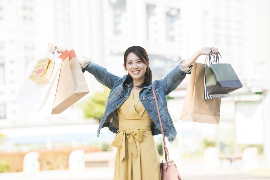 女子露出笑臉兩手提著許多購物袋子