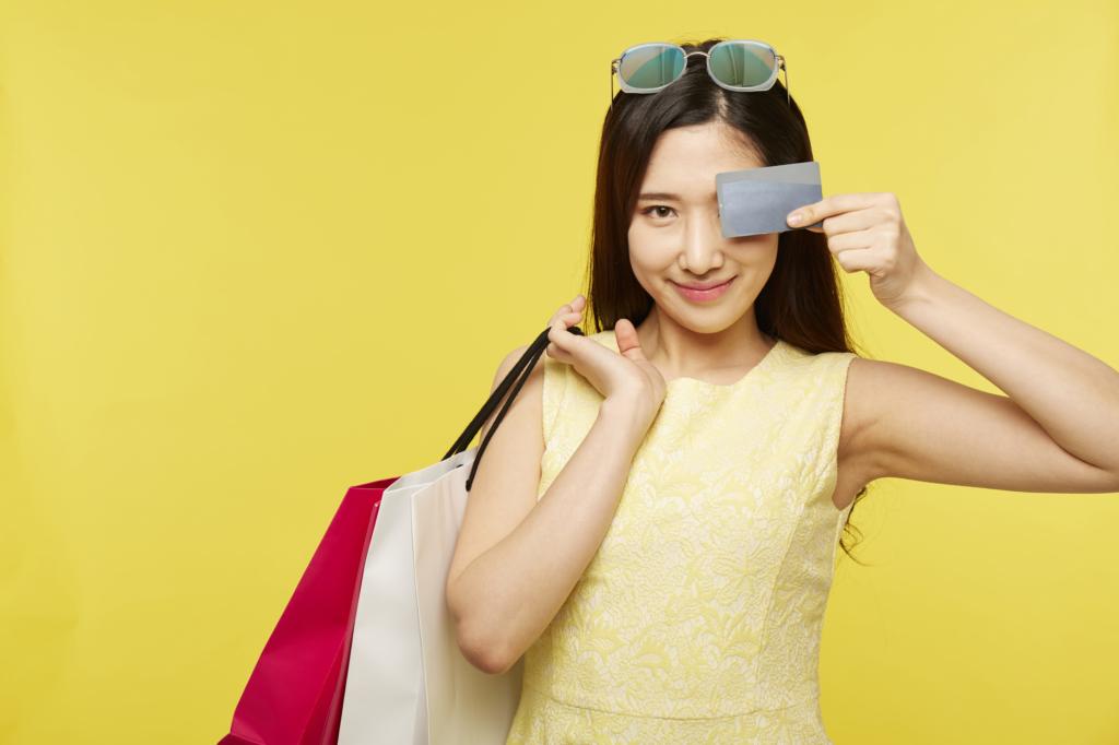 女子一手拿著購物袋一手拿著信用卡遮眼