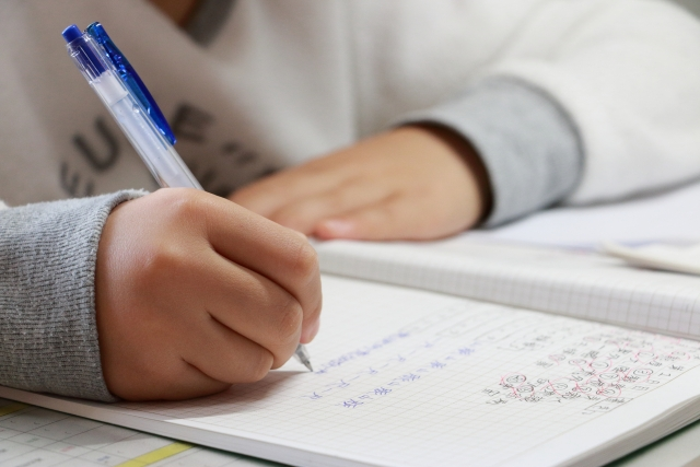 手握藍筆在筆記本上寫字