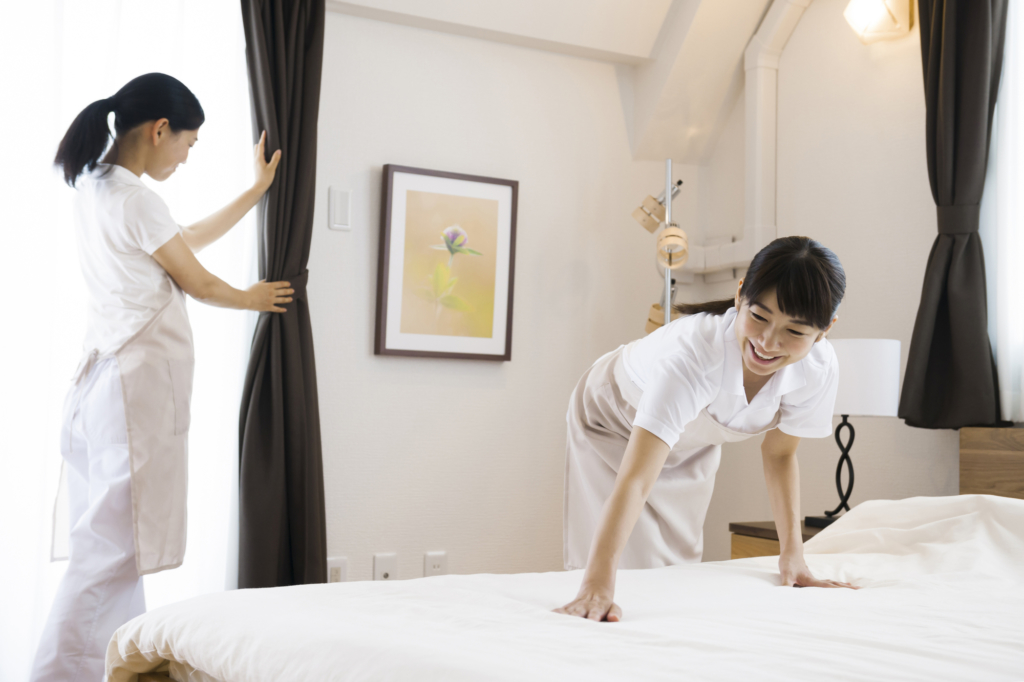 Two hotel employees clean a hotel room