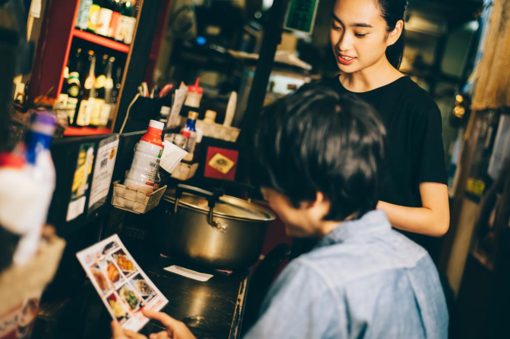 A staff member takes an order at an izakaya