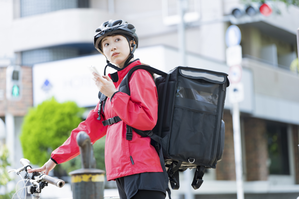 A food delivery driver searches for an address