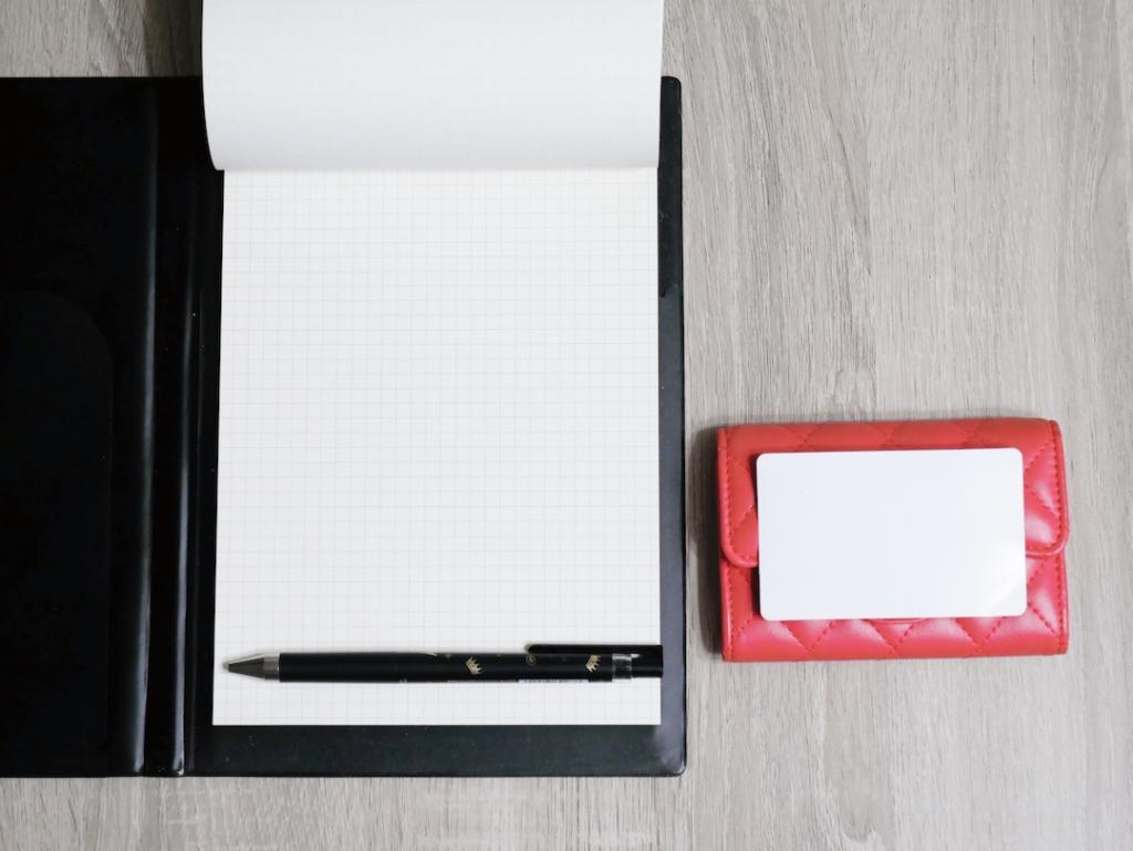 桌子上放著掀開的空白筆記本和放在名片夾上的名片