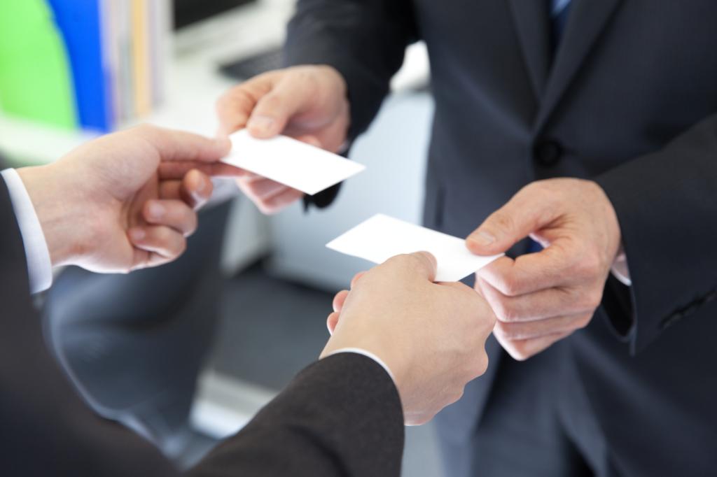 兩位穿著西裝的男子正在交換名片一手握著自己的名片左手準備拿對方的名片