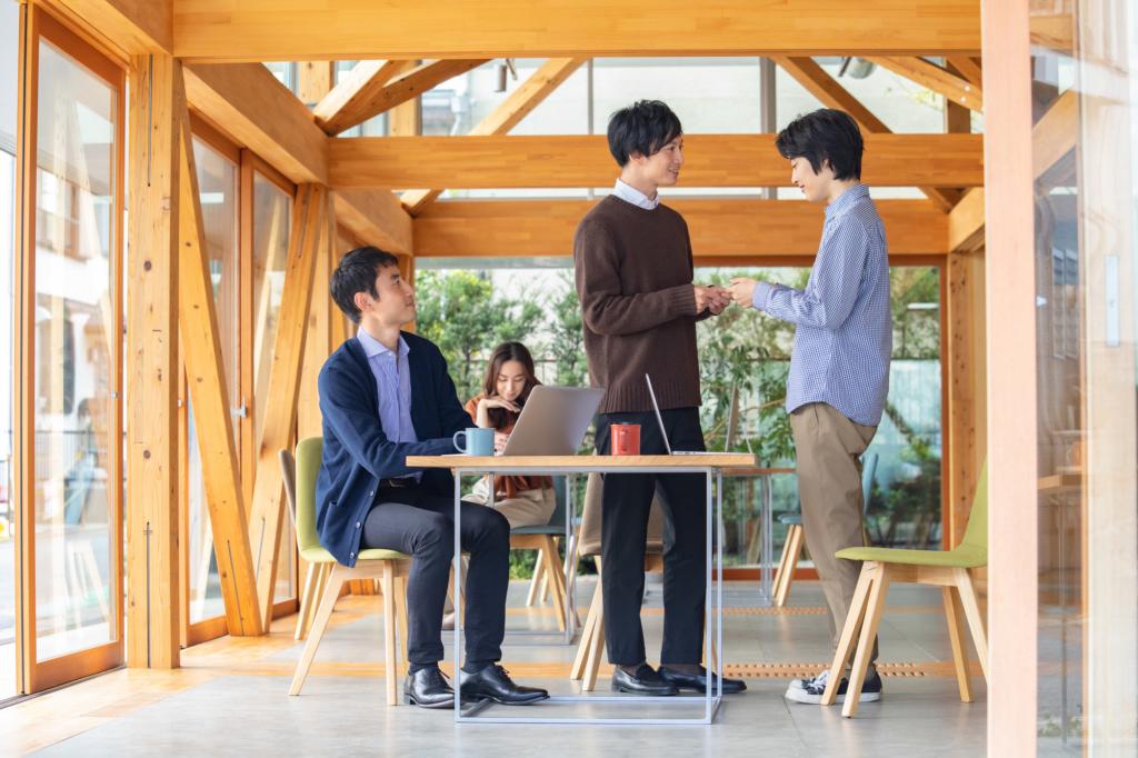木造空間裡兩位男子起身在桌旁交換名片