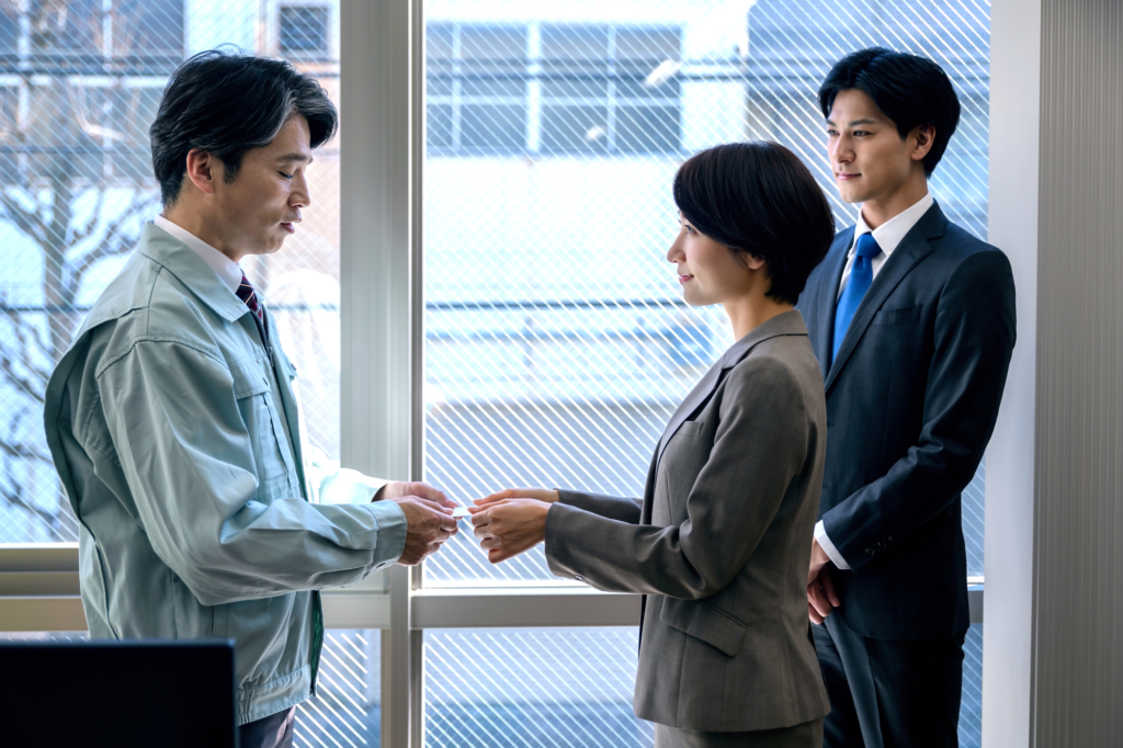 套裝女子正遞著自己的名片給穿著工作服的客人男子