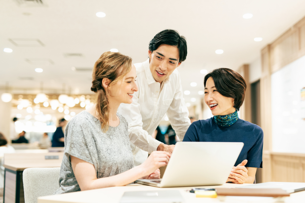 開放的辦公室空間裡一男兩女正在對著筆電開心討論