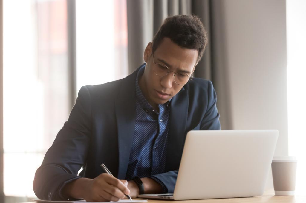 帶著眼鏡的西裝男子正倚靠著桌子寫字