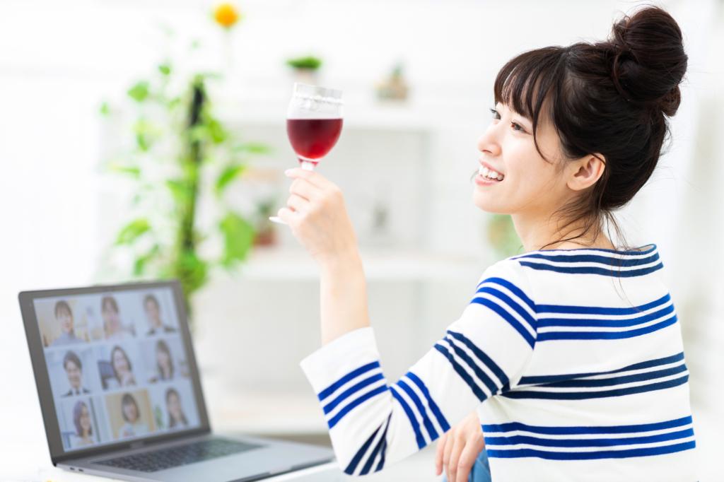 Nhân viên uống rượu trong bữa tiệc trực tuyến của công ty