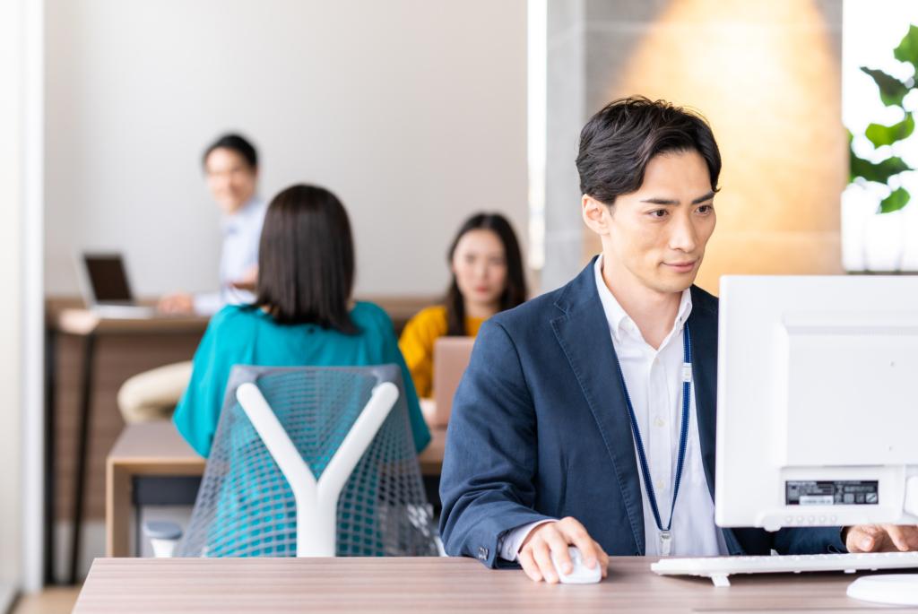 辦公室裡穿著西裝的男子坐在電腦前使用電腦 背後有群同事