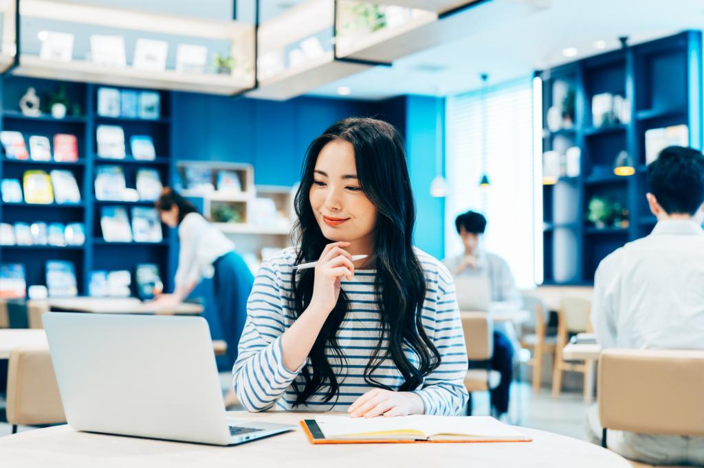開放式的辦公空間裡穿條紋衣的長髮女子正在對著筆電若有所思